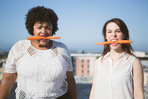 Two women chomp carrots